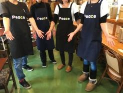 「ウエルカム!」の気持ちを表す女性スタッフ。「Peace」エプロンをつけて、一緒に働いてみませんか。
